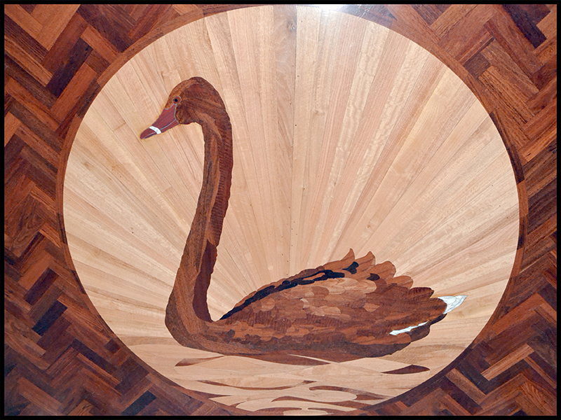 Inlaid image of a swan in wooden floor