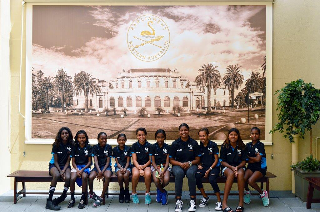 Students from One Arm Point Remote Community School seated against a banner of Parliament House