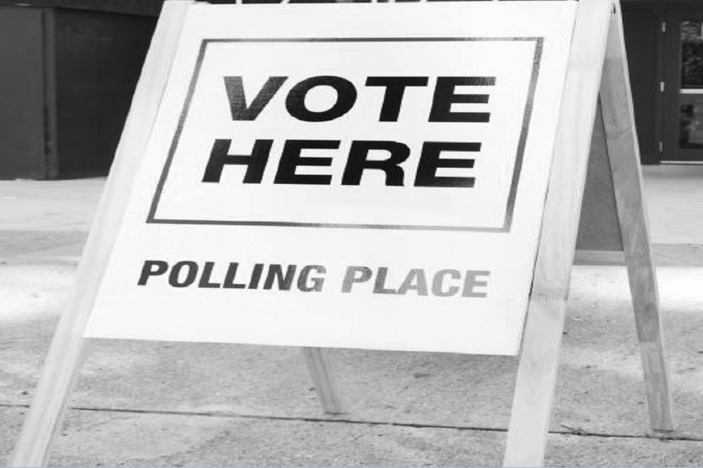 'Vote here, polling place' written on a sign